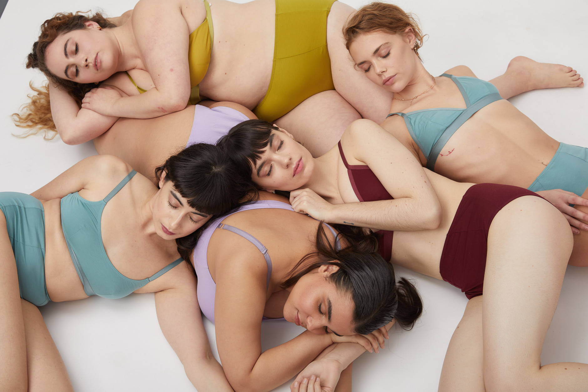 Portrait of 5 real women models in colored underwear and bra laying down for Jonsey