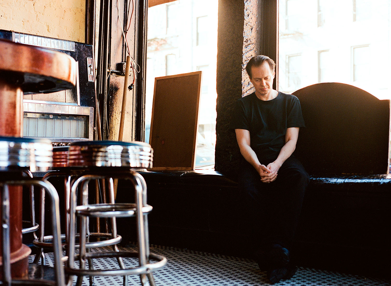 Steve Buscemi in black t-shirt at an empty bar, by Abbey Drucker