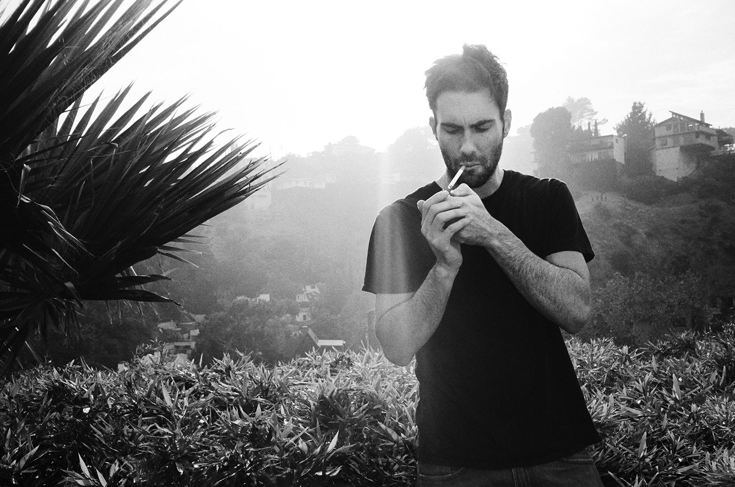 Adam Levine, lead singer of Maroon 5 smoking cigarette on Los Feliz Los Angeles hike by Abbey Druckerin black and white