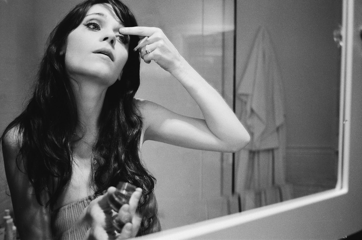 Zoe Deschanel applying makeup in bathroom mirror by Abbey Drucker in black and white