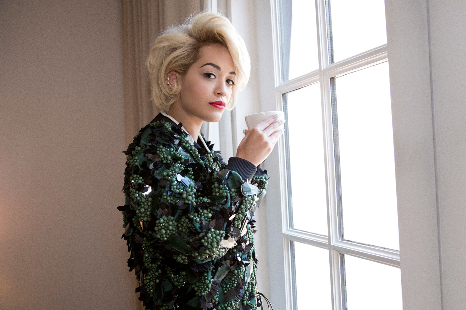 Rita Ora drinking coffee in red lipstick and a blonde bob, wearing a green sequin beaded jacket looking out window by Abbey Drucker for Glamour Magazine